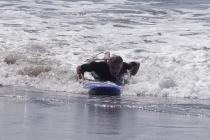 Ein Surfer rutscht auf seinem Brett