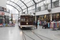 Tram fährt durch kleines Einkaufszentrum