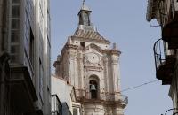 Spitze eines Kirchturms der zwischen Häusern durch scheint