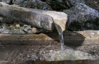 Wasserspendender Holzbrunnen