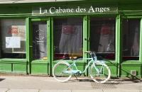 Grünes Geschäft mit altem, blauen Fahrrad davor