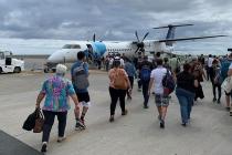Eine ganze Menschentraube auf dem Weg zum Flugzeug