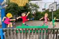 Fußballspielende Kinder auf buntem Zaun
